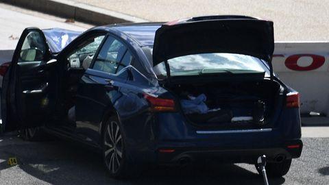 Ein dunkelblauer BMW steht mit offenem Kofferraum, Fahrertür und Motorhaube zerstört an einer Beton-Barriere