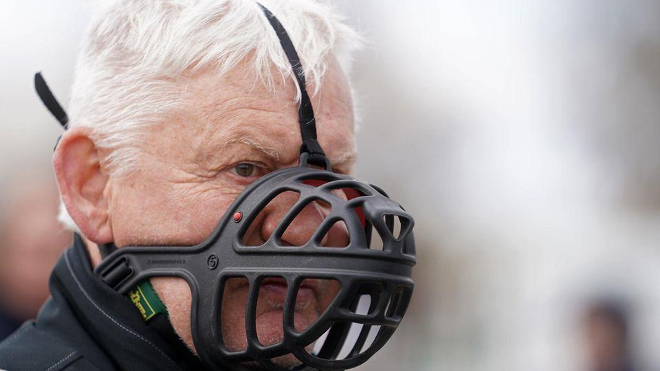 Ein weißhaariger älterer Mann trägt statt einer FFP2-Maske einen schwarzen Maulkorb für Hunde