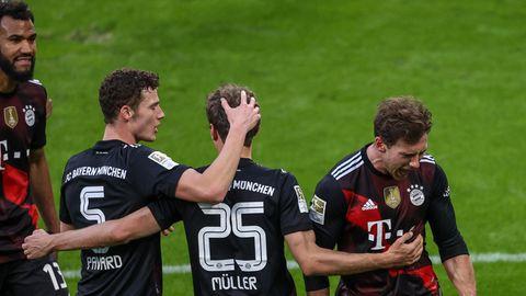 Vier Spieler des FC Bayern München jubeln auf dem Rasen des Bundesliga-Stadions in Leipzig