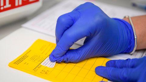 Eine linke Hand in blauem Gummihandschuh hält einen gelben Impfpass, in den die rechte Hand einen Aufkleber einklebt