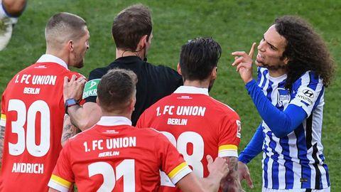 Herthas Matteo Guendouzi muss sich gegen die Proteste der Union-Spieler wehren, die ihm ein hartes Foul vorwerfen