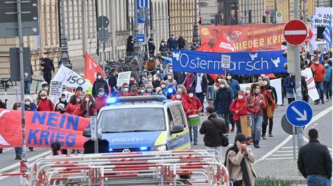 Teilnehmer gehen beim Ostermarsch mit Bannern, Fahnen und Plakaten durch München
