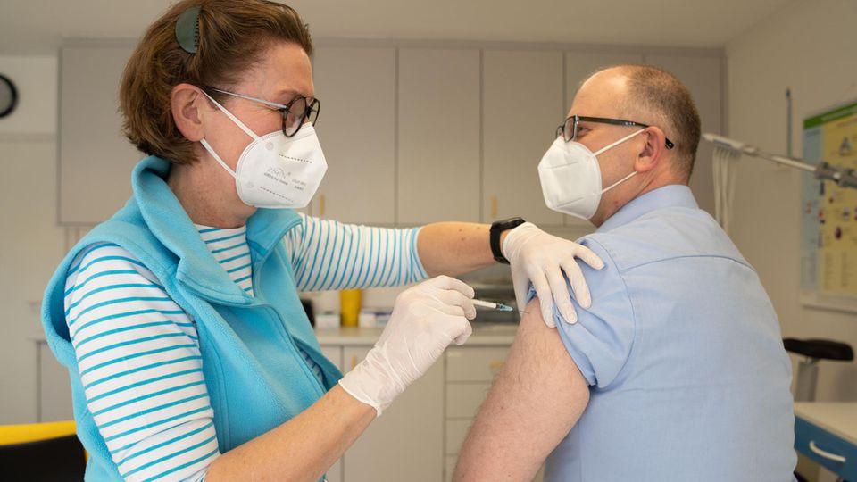 Eine Ärztin gibt einem Patienten eine Injektion