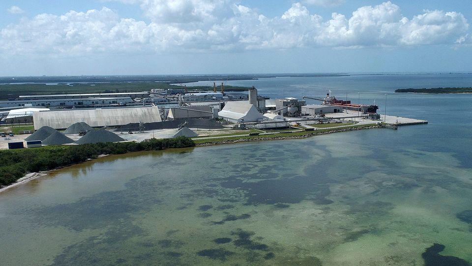 Am Ufer eines Sees ist eine riesige Fabrik zu sehen
