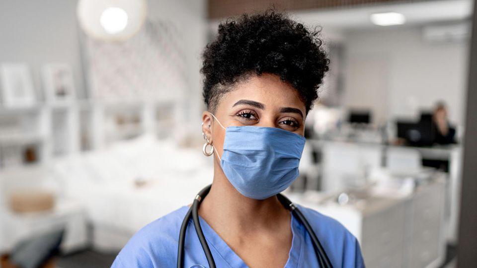 Gehalt Pflege: Eine Pflegekraft mit Mundschutz