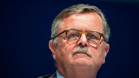 Ein Mann mit angegrautem Seitenscheitel und Schnauzbart sowie einer Hornbrille schaut von oben in die Kamera