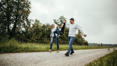 Eltern läuft mit Kind an der Hand durch ein Feld