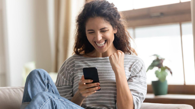 Ein günstiges Smartphone macht einer Frau Freude.