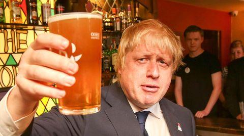 Ein blonder, propperer Mann im Anzug erhebt ein Pint-Glas mit Bier, während er in einem englischen Pub steht