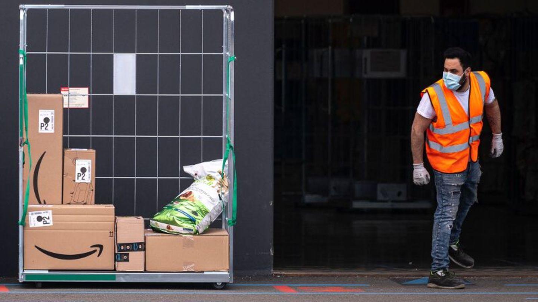 Ein Amazon-Mitarbeiter neben einem Haufen Paketen der Firma