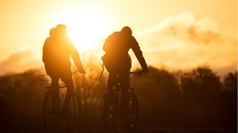 Bremen, Deutschland.Um 6.42 Uhr ist heute in der Hansestadt die Sonne aufgegangen. Diese Radfahrer waren da schonam Werdersee unterwegs – und wurden für ihr frühes Aufstehen mit einem herrlichen Anblick belohnt.