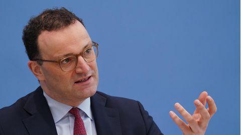 Ein Mann mit braunen Locken und durchsichtigem Brillengestell sitzt im Anzug vor einer blauen Wand und gestikuliert mit links