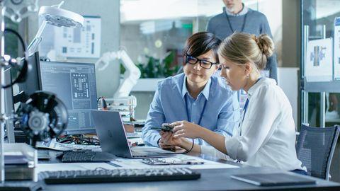 Zwei Frauen bei der Reparatur eines Laptops. Ein Feld zur Passwort-Eingabe ist nicht zu sehen