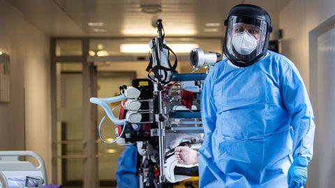 Ein Mann in medizinischem Vollschutz zieht ein Bett mit einem beatmeten Patienten über einen Krankenhaus-Flur