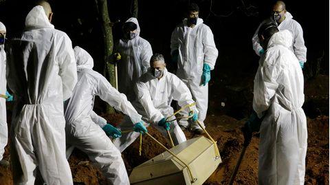 Sieben Männer in weißen Schutzanzügen senken einen hellen Holzsarg mit einem Corona-Toten in ein Grab