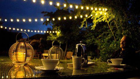 Gartenbeleuchtung: Mann sitzt in der Dämmerung an einem gedeckten Tisch mit Deko-Lampen