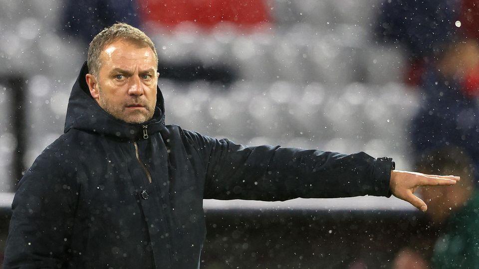 Ein Schneetreiben steht ein Mann im Anorak am Rande eines Fußballplatzes und zeigt etwas mit ausgestrecktem linken Arm