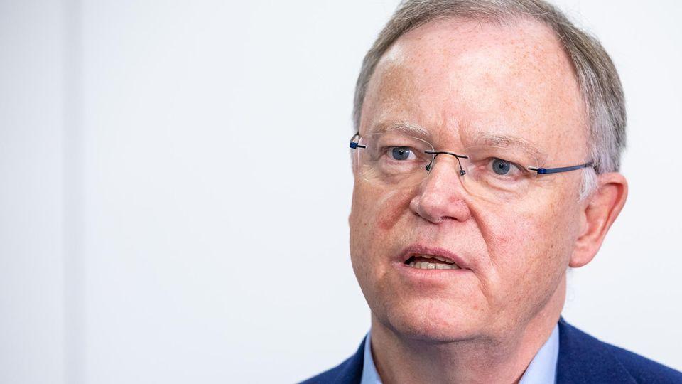 Ein Mann mit grauem Seitenscheitel und randloser Brille egt beim Sprechen den Kopf leicht schräg. Er trägt einen blauen Anzug