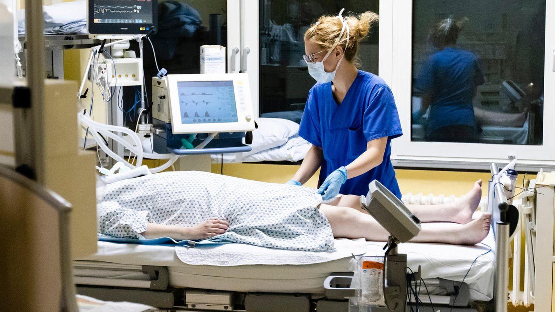 Eine Krankenschwester in blauer Krankenhaus-Kleidung steht mit Mundschutz am Bett einer Corona-Patientin auf der Intensivstation