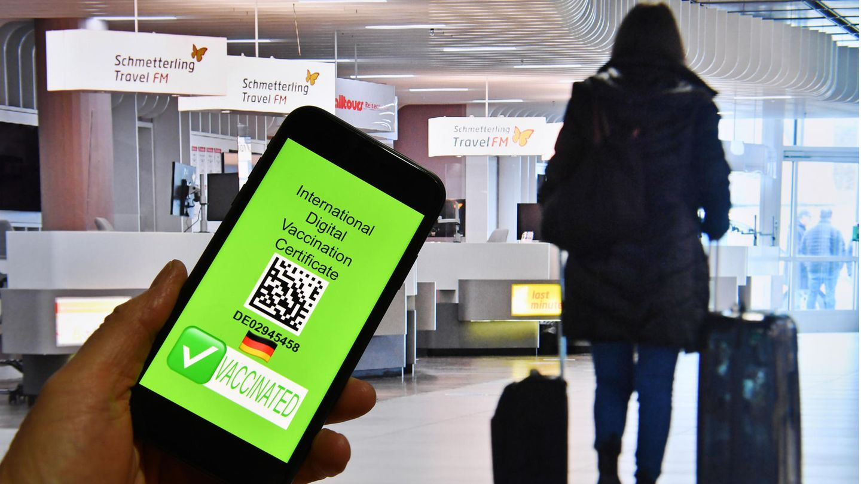Eine Hand hält ein Handy, dahinter ist eine Szene im Flughafen zu sehen