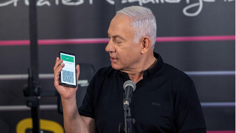 Israels Ministerpräsident Benjamin Netanjahu hält ein Smartphone in der Hand mit der geöffneten App des Grünen Passes