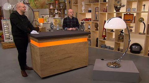 Sven Deutschmanek und Horst Lichter stehen im Studio von Bares für Rares neben einer riesigen Leuchte