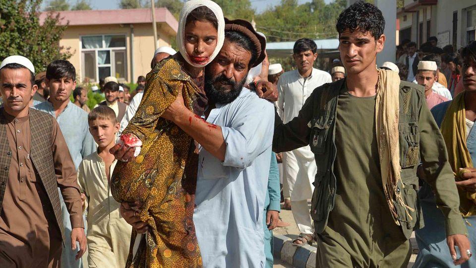 Nach einem Autobomben-Angriff der Taliban auf ein Regierungsgebäude im Oktober 2020 trägt ein Mann ein verletztes Mädchen zum Krankenhaus des Distrikts Ghani Khel nahe der afghanischen Stadt Jalalabad.