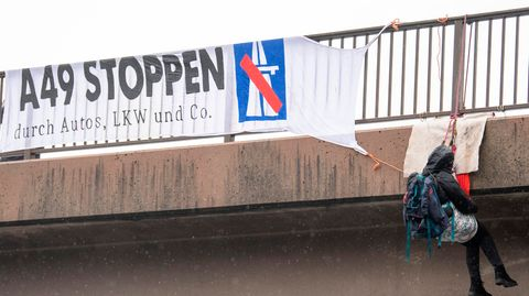 Gegner des Ausbaus der A49 haben sich von einer Brücke über die Autobahn 5 am Flughafen Frankfurt abgeseilt