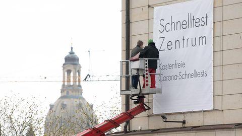 """Mitarbeiter installieren an der Fassade des Bilderberg Bellevue Hotel einen Banner mit der Aufschrift """"Schnelltest Zentrum"""""""
