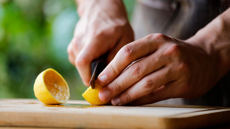 Mann schneidet Zitrone