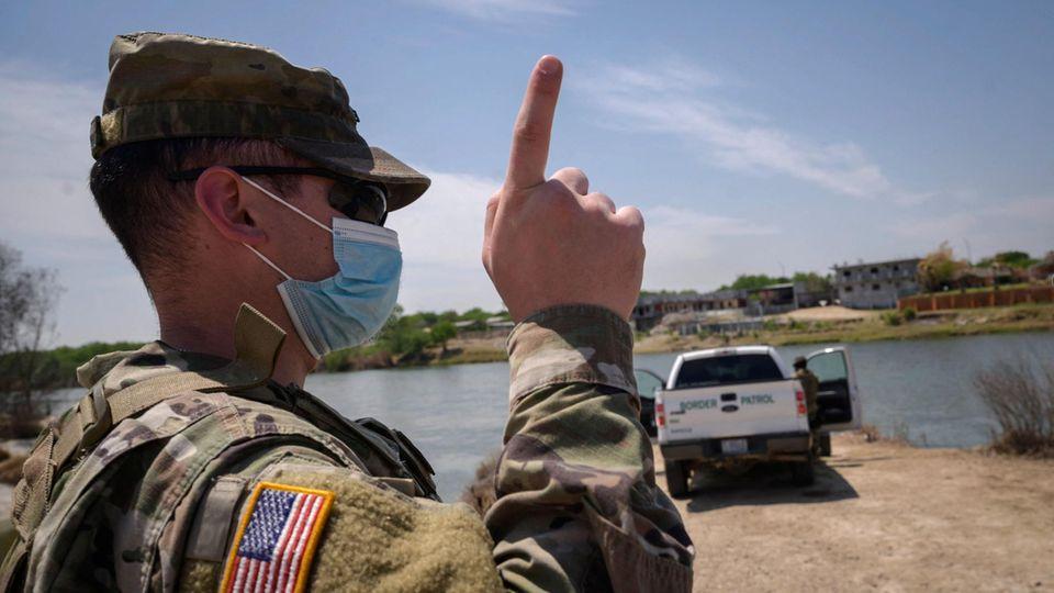 Ein Uniformierter mit US-Flagge auf dem rechten Ärmel steht in einer Wüste und hebt den Zeigefinger. Im Hintergrund ein Pickup