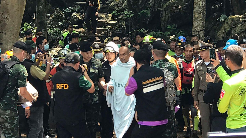 Der gerettete Mönch wird von zahlreichen Rettungskräften aus der Höhle geführt.