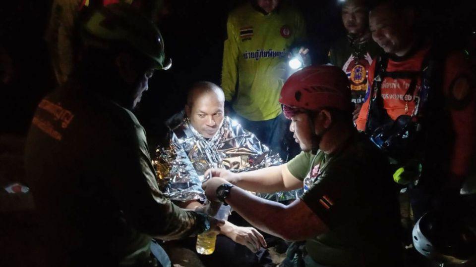 Der gerettete Mönch wird in eine Wärmedecke gehüllt von den Rettungskräften mit Flüssßigkeit versorgt