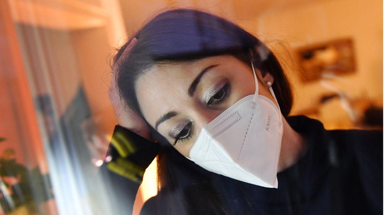 Frau mit FFP2-Maske schaut aus einem Fenster