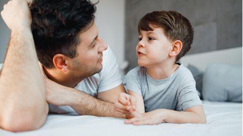 Vater und Sohn liegen auf dem Bett, der Junge redet