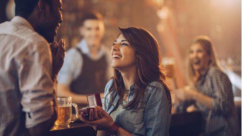 Frau macht ihrem Freund in einer Bar einen Heiratsantrag, indem sie ihm eine Schachtel mit einem Ring hinhält