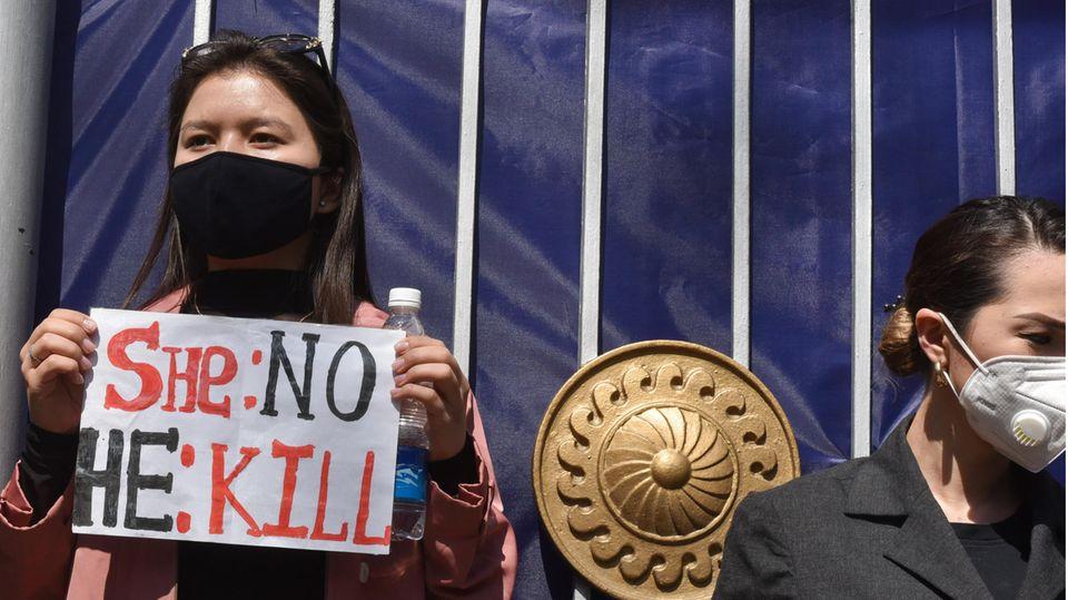"""Eine Frau steht mit Maske und Schild vor einem Tor. Auf dem Schild steht: """"She: no - He: kill"""""""