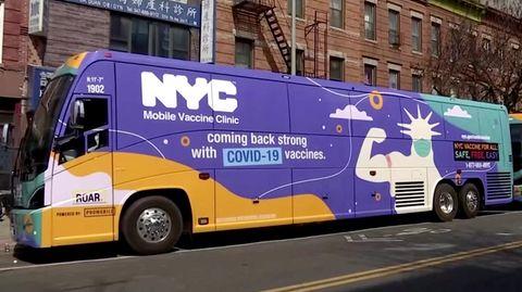 Ein gelb-lila-grüner Reisebus steht vor einem klassischen New Yorker Backstein-Gebäude mit Feuerleitern an der Fassade