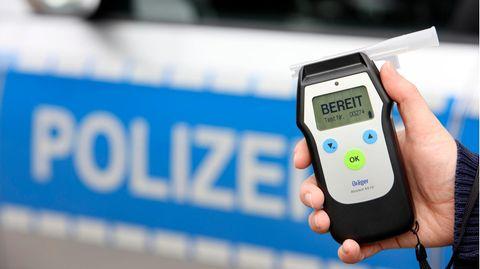 Polizist mit Atemalkohol-Messgerät zur Überprüfung der Fahrtüchtigkeit eines Autofahrers