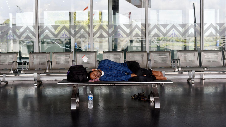 Ein Passagier schläft auf einem indischen Flughafen