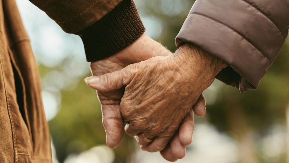 Älteres Paar hält sich an den Händen