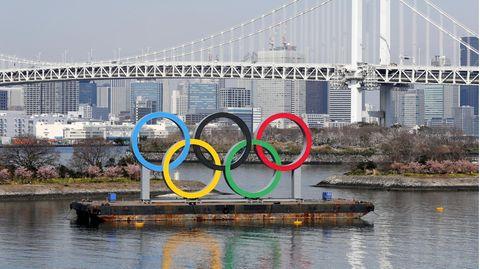 Die Ringe der Olympischen Spiele stehen vor dem Regenbogenbrücke im Odaiba Marine Park in Tokio