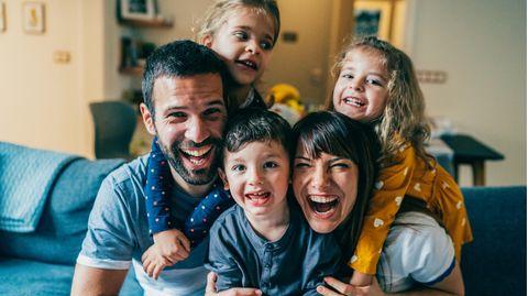 Eine fünfköpfige Familie lächelt in die Kamera