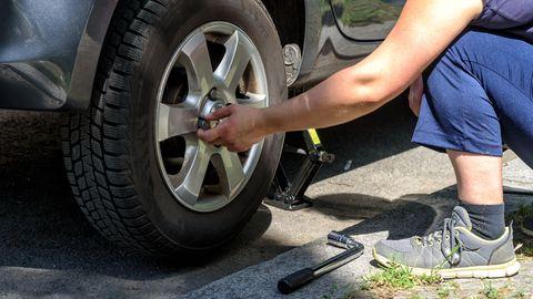 Reifenwechsel trotz Corona: Mann löst die Radmuttern beim Reifenwechsel