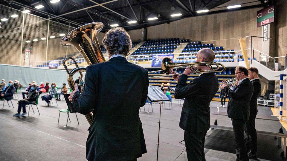 Musiker desSymphonieorchester Aalborg spielen, während Menschen im Impfzentrum geimpft werden