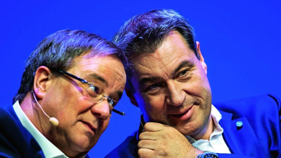 Armin Laschet neben Markus Söder vor einem blauen Hintergrund