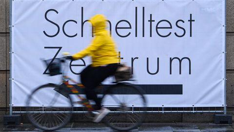 Eine Person mit gelber Jacke radelt am Schild für ein Schnelltest-Zentrum vorbei