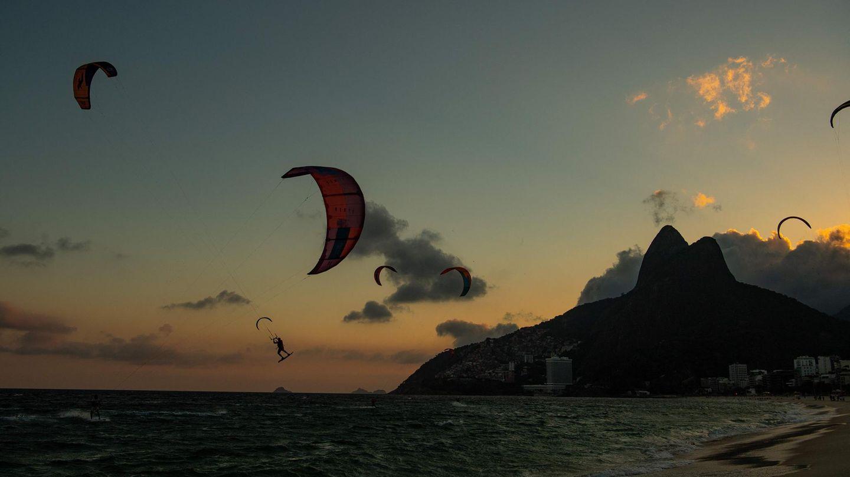 Rio de Janeiro, Brasilien. Während hinter den Dois Irmãos, den zwei Brüdern, wie die Berge im Hintergrund genannt werden, die Sonne untergeht, nutzen Kitesurfer am Strand von Ipanema noch das letzte Licht des Tages, um ihrer Leidenschaft nachzugehen.