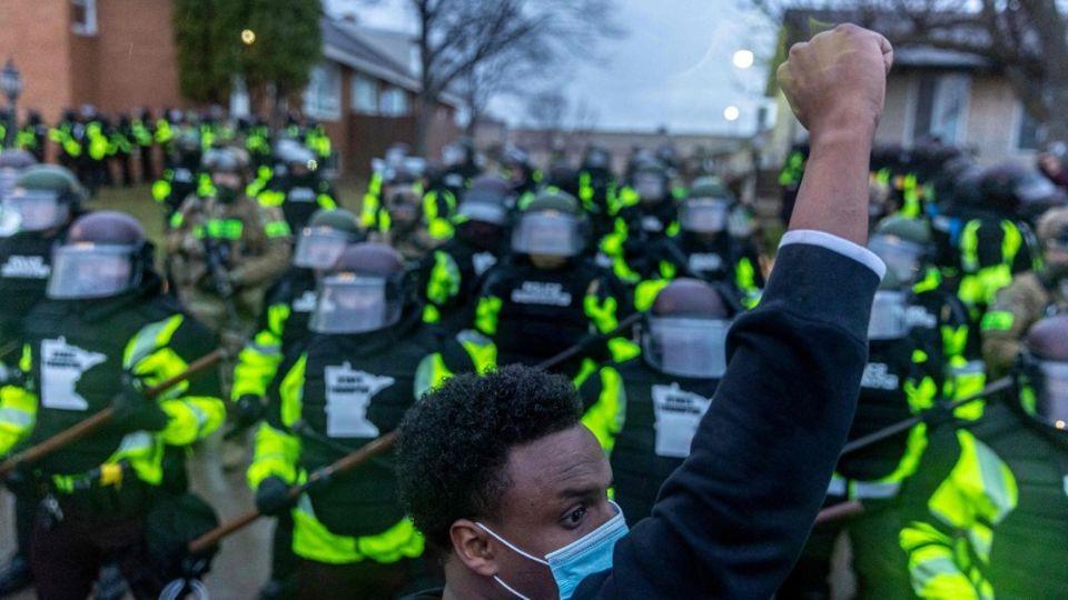 Ein junger schwarzer Mann mit Gesichtsmaske protestiert, dahinter sind Polizisten zu sehen