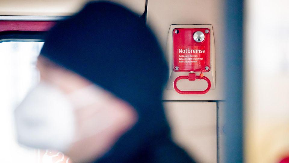 Ein Fahrgast mit Mund-Nasen-Schutz steht in einer Berliner S-Bahn vor einer Notbremse